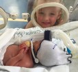 Oliver in his incubator after his premature birth with big sister Isabella by his side.