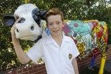 Hillcrest Christian College student Colby with the school's resident fibreglass cow. The college in Clyde North will receive $1.71 million, to put towards a discovery centre and administration building.